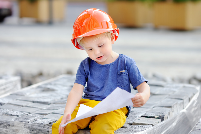 Portrait of little builder in hardhats reading construction drawing. Little boy`s dream concept