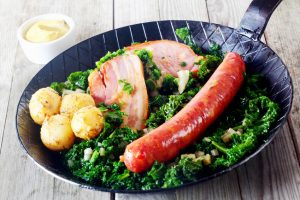 Close up Gourmet German Cuisine on Frying Pan, Emphasizing Cooked Sausage, Meat and Potatoes on Kale Veggies, with Mustard on Side