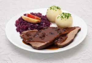 Sauerbraten mit Rotkohl und Knödeln - Tellergericht auf weißer Tischdecke