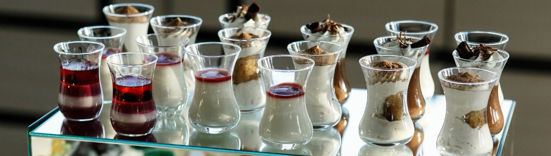 Glasses with tiramissu and other cold desserts stand on glass box