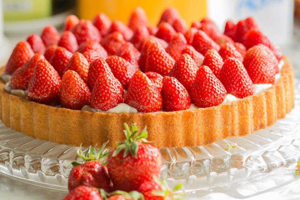 Ganze Erdbeeren auf einem Kuchenboden angeordnet und mit Tortenguss bedeckt